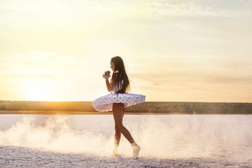 Tender young ballerina dancer in a snow-white tutu dress and white pointe shoes on a salty dried lake. Fantastic landscape and a girl  ballerina