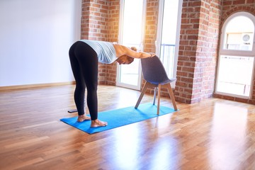 Middle age beautiful sportwoman standing on mat. Practicing yoga doing down dog on chair pose at gym