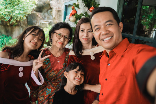 big family selfie on christmas day. asian people take picture using mobile phone