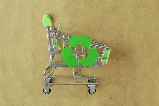 Green shopping cart with recycle symbol on recylced paper - Concept of ecology and responsible shopping
