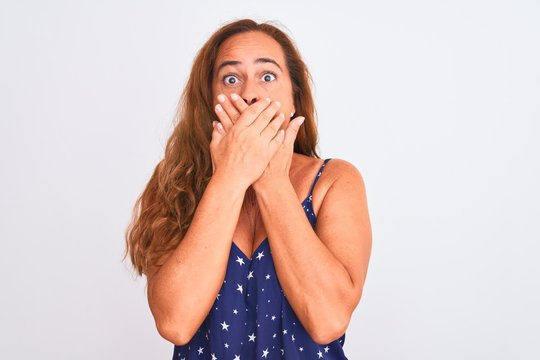 Middle age mature woman standing over white isolated background shocked covering mouth with hands for mistake. Secret concept.
