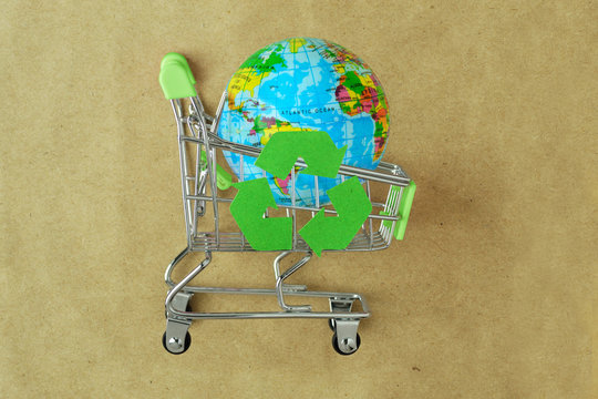 Earth planet in green shopping cart with recycle symbol on recylced paper - Concept of ecology and responsible shopping