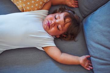 Beautiful toddler child girl wearing white bodysuit lying down on the sofa