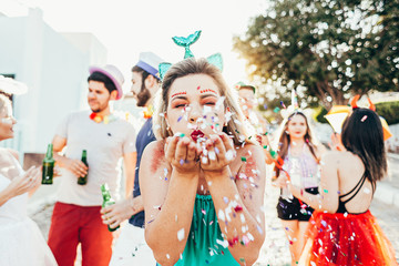 Brazilian Carnival. Young woman in costume enjoying the carnival party blowing confetti Wall mural