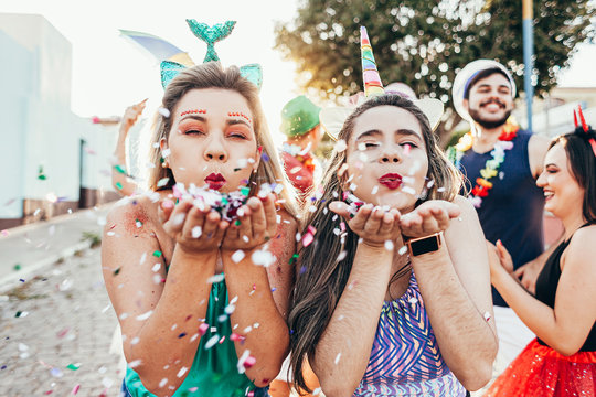 Brazilian Carnival. Young women in costume enjoying the carnival party blowing confetti