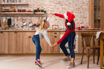 Woman and a girl dancing on Christmas eve