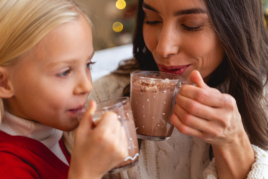 Child and her mother enjoying hot chocolate