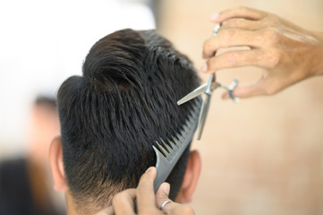 The male barber is cutting the male customer in the barber shop