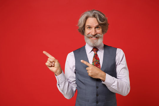 Smiling elderly gray-haired mustache bearded man in classic shirt vest colorful tie isolated on red background in studio. People lifestyle concept. Mock up copy space. Pointing index fingers aside.