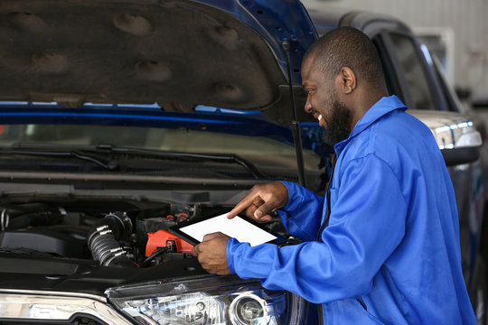 African-American mechanic with tablet computer working in car service center