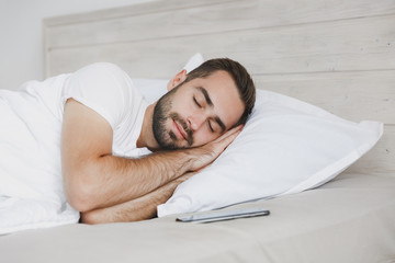 Calm young handsome bearded man lying in bed with white sheet pillow blanket in bedroom at home....