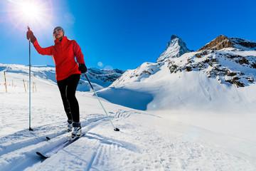 Woman cross country skiing on a sunny winter morning in Swiss Alps, Zermatt.