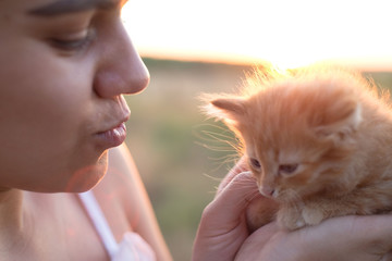 Portrait of a girl, surprised, holding a cute little kitty. Concept of goodness and love