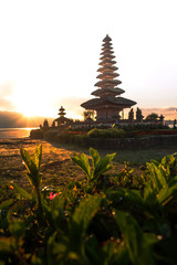 Beautiful famous touristic Pura Ulun Danu Pagoda in Bali during the sunrise with red flowers. Touristic place in Indonesia