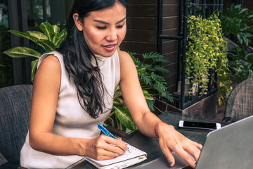Asian woman writing on a book. Business woman using a laptop