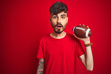 Young athlete man with tattoo holding football ball standing over isolated red background scared in shock with a surprise face, afraid and excited with fear expression