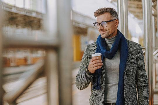 Handsome elegant gentleman holding cup of coffee