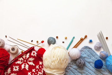 Balls of wool yarn for hand knitting and crochet, sets of knitting needles and hooks on a white background. The concept of crafts and hobbies. Flat lay, copy space, close-up, mock up, blank for ad