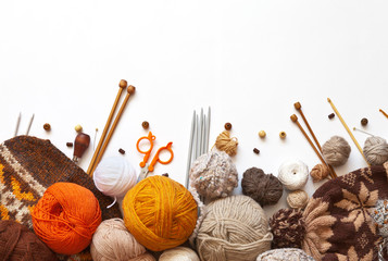 Tangles of orange, brown and beige wool yarn for hand knitting, accessories for knit, and knitted hats on a white background. The concept of crafts and hobbies. Copy space, flat lay, mock up