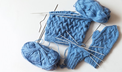 Needlework. The process of hand knitting warm hat and mittens for the winter of natural blue mohair yarn with volumetric pattern of braids, circular knit on five needles. Copy space, flat lay