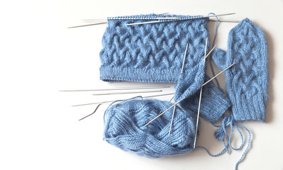 The process of circular knitting of warm mittens and hats for the winter of natural blue mohair yarn with a three-dimensional pattern of braids. Light background, top view, space for text, flat lay