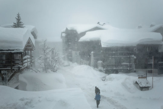 Heavy snow storm at Val d'Isere, Savoie of France. Buildings covered with snow during hard winter conditions on January at French Alps.