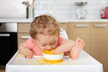 Baby in high chair eating pasta straight from bowl