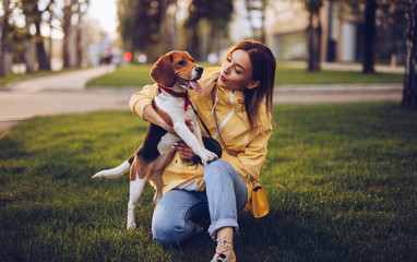 Careful woman looking at dog while hugging in green grass Wall mural