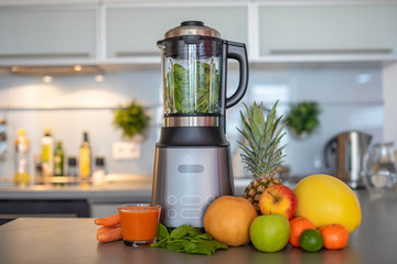 Making green smoothies with blender in home kitchen, healthy eating lifestyle concept
