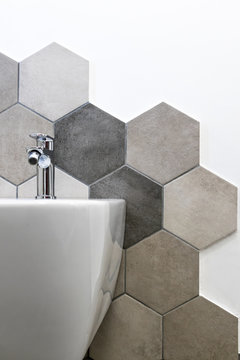Interior of a house, private bathroom. hexagonal tiles with natural colors on gray brown in a bathroom. interior furnishings and supplies, majolica mounted on the wall near a bidet.