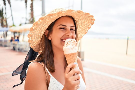 Young beautiful woman eating ice cream cone by the beach on a sunny day of summer on holidays