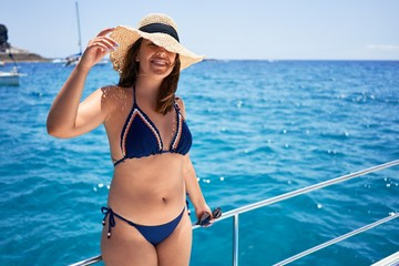 Young beautiful woman smiling happy, sailing on a boat on a sunny day on holidays