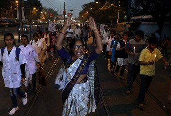 A woman shouts slogans as she takes part in a candle light vigil to protest against the alleged rape and murder of a 27-year-old woman, in Kolkata