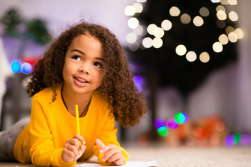 Pensive cute little afro girl thinking about gift ask from Santa