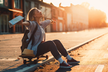 Smiling girl sitting on long board in the city during sunset with arms outstretched. Fotomurales