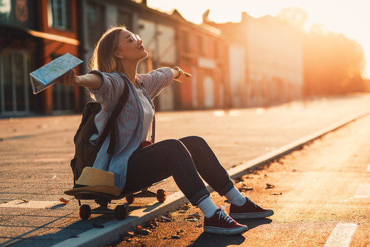 Smiling girl sitting on long board in the city during sunset with arms outstretched.