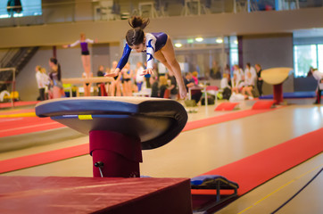Young gymnast girl performing jump