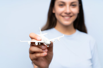 Young woman over isolated blue wall holding a toy airplane