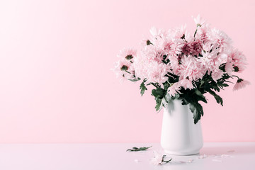 Fresh bouquet of pink flowers in vase on white shelf on pink wall background. Floral home decor.