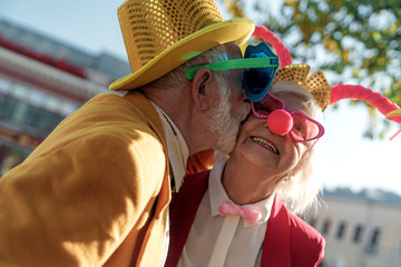 Aged man in clown costume kissing wife outdoors stock photo