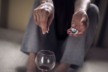 Papiers peints Bar a young girl sitting in a dirty room, with a glass of wine, and holds pills in her hand. Poisoning when mixing alcohol and drugs. Polydrug addiction in women