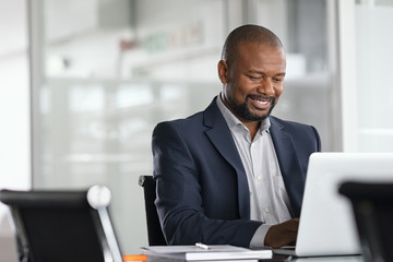 Black mature businessman working on laptop Fotobehang