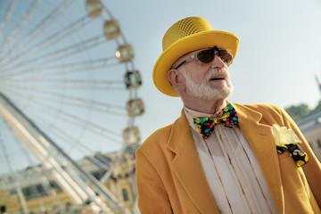 Happy old man near ferris wheel stock photo