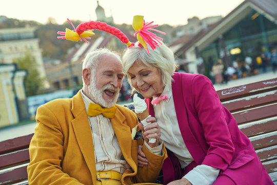Loving mature couple with ice cream outdoors stock photo
