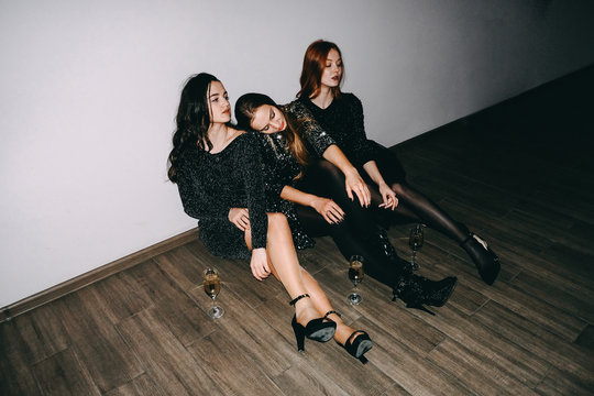 After party, jet set, clubbing, nightlife concept. Tired girls with glasses of champagne sit on the floor after celebrating party