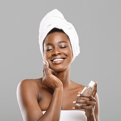 Fototapete - African girl cleaning skin with cotton pads and face toner after bath