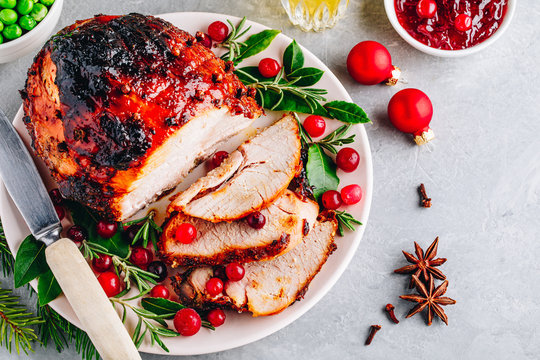 Christmas Glazed Ham with cranberry sauce. Roasted Holiday Pork Meat.