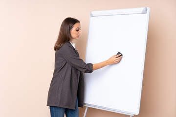 Young woman giving a presentation on white board giving a presentation on white board