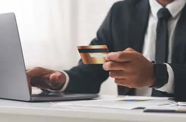 Cropped photo of businessman using laptop and holding credit card