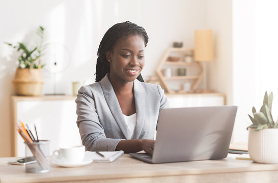Smiling afro businesswoman working on laptop in modern office